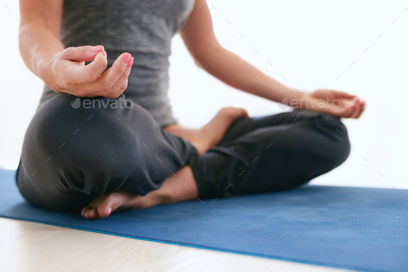 Woman in Lotus pose on exercise mat at gym - Stock Photo - Images
