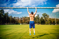 atheltic man doing chinups and core training in park. football player training on grass court - PhotoDune Item for Sale