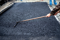 Worker leveling fresh asphalt on a road construction site, industrial building - PhotoDune Item for Sale