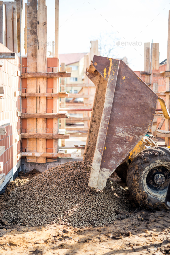 Dumper truck unloading construction gravel, granite and crushed stones at building foundation - Stock Photo - Images