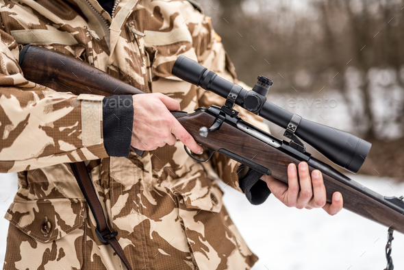 Close up and details of a man wearing a camouflage suit holding a sniper, rifle or gun - Stock Photo - Images