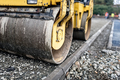 Heavy tandem road roller compacting layers of gravel on road construction site. - PhotoDune Item for Sale
