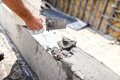 Construction worker leveling concrete with putty knife at building site. - PhotoDune Item for Sale