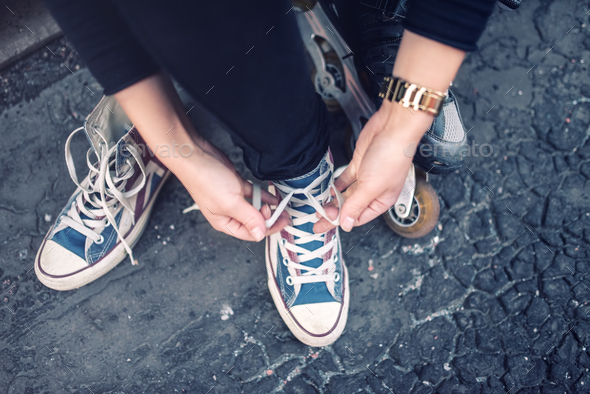 Hipster wearing sneakers, teenager tying laces at sport shoes. Urban lifestyle with footwear - Stock Photo - Images