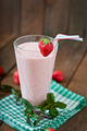 Strawberry milkshake smoothie with fresh strawberry on a wooden background