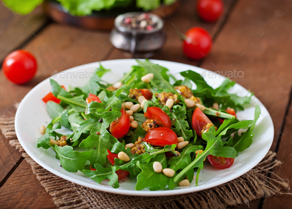 Salad with arugula, tomatoes and pine nuts - Stock Photo - Images