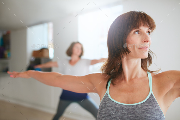 Woman doing the warrior pose during yoga class - Stock Photo - Images
