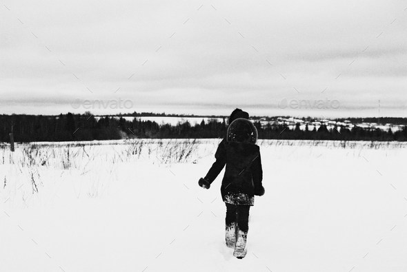 Two figures walk into the snow - Stock Photo - Images