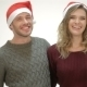 Happy Couple In Santa Hat Laughs While Standing In - VideoHive Item for Sale