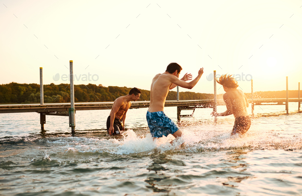Three teenage boys playing in the water - Stock Photo - Images