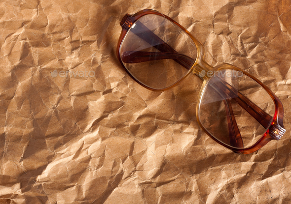 Antique glasses on old crumpled paper - Stock Photo - Images