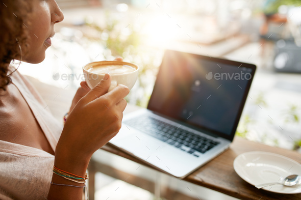 Woman drinking coffee with a laptop at restaurant - Stock Photo - Images