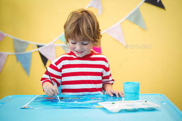 Smiling boy painting a picture at the desk - Stock Photo - Images