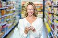 Smiling woman using smartphone in supermarket - PhotoDune Item for Sale