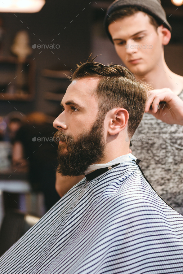 Professional hairdresser cutting bearded man's hair - Stock Photo - Images
