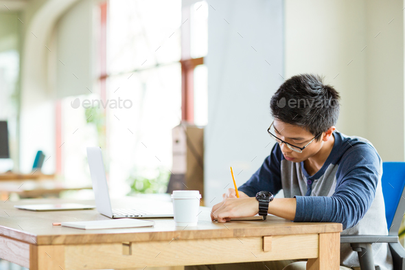Young serious asian man writing in notebook and using laptop - Stock Photo - Images