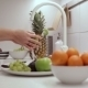 Woman Washes a Green Apple In The Kitchen Sink - VideoHive Item for Sale