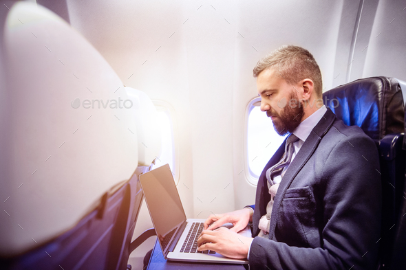 Businessman in airplane - Stock Photo - Images
