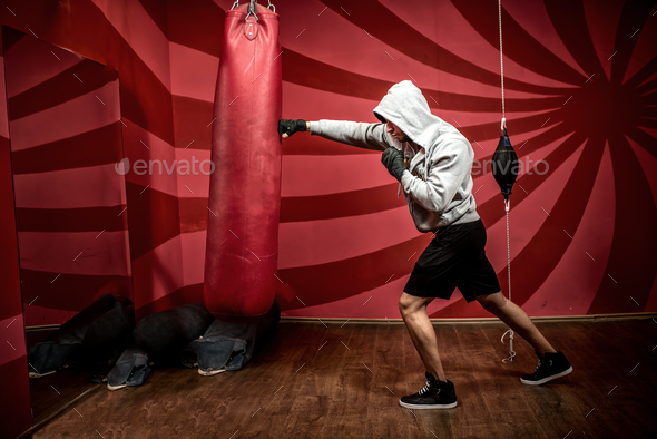 Athlete with hoody working out at boxing gym, getting ready for fight - Stock Photo - Images