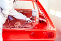 Close-up of spray paint gun with worker working on a red car - PhotoDune Item for Sale