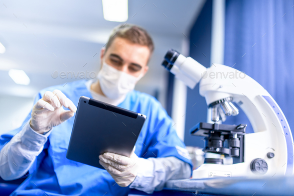 pharmacist working on prescription drugs with modern tablet and microscope - Stock Photo - Images
