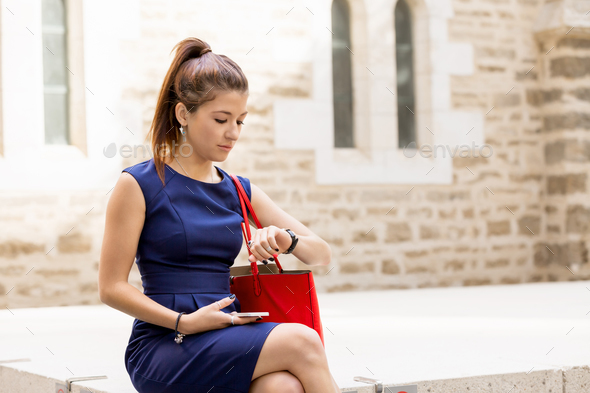 Pretty business woman looking at her watch - Stock Photo - Images