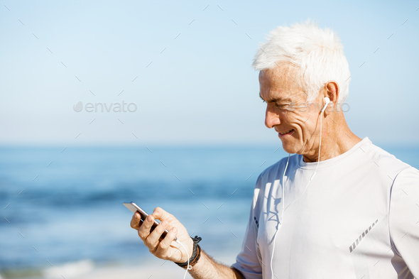 Male runner with his mobile smart phone standing outdoors - Stock Photo - Images