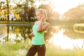 Woman with mobile phone getting ready for training in urban park - PhotoDune Item for Sale