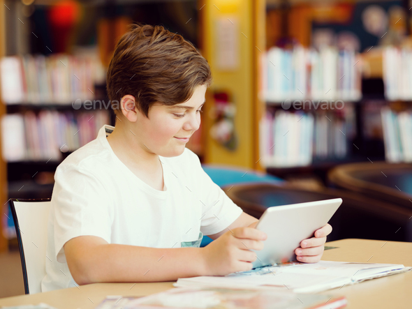 Teenage boy with tablet in library - Stock Photo - Images