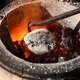 The Blacksmith Straightens the Crucible in the Furnace with a Poker - VideoHive Item for Sale