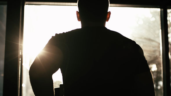 Male Silhouette Against Sun Running On Treadmill In A Gym By