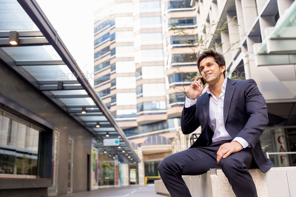 Portrait of confident businessman with mobile phone outdoors - Stock Photo - Images