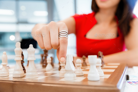 Business woman sitting in front of chess - Stock Photo - Images