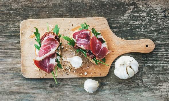 Brushetta set with smoked meat, arugula, garlic and dried tomato - Stock Photo - Images