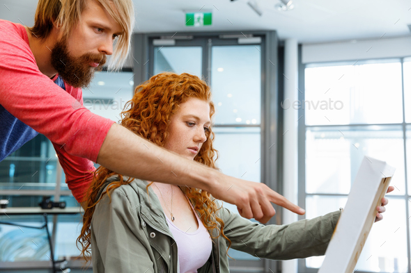 Young caucasian couple standing in a gallery and contemplating artwork - Stock Photo - Images