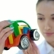 Woman Employee To Look At The Color Plastic Toy Tractor - VideoHive Item for Sale