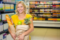 Smiling woman standing in aisle with grocery bag at supermarket - PhotoDune Item for Sale