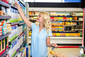 Smiling woman with cart taking food from shelf in supermarket - PhotoDune Item for Sale