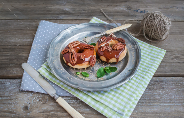 Cinnamon donuts with caramel icing and pekans served with fresh - Stock Photo - Images