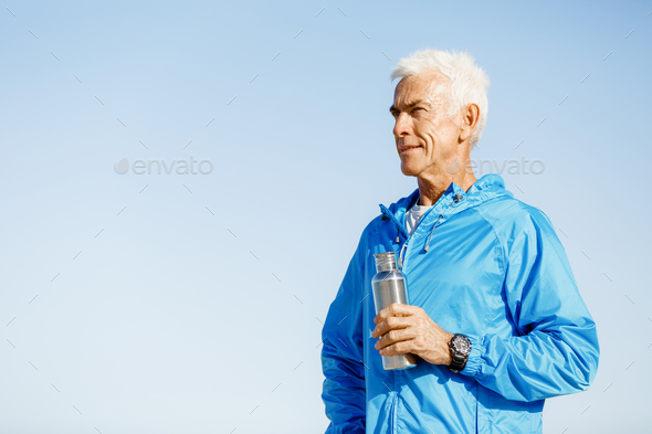 Confident man holding bottle with water - Stock Photo - Images