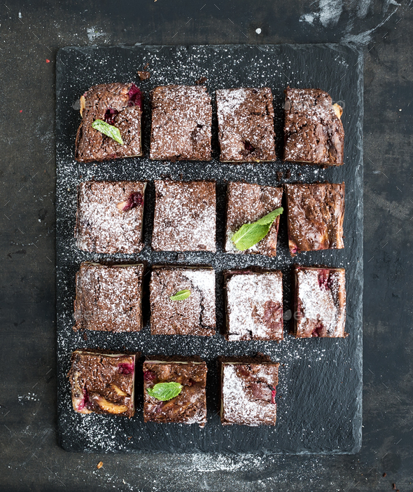 Chocolate and raspberry brownie squares on black stone board over dark grunge backdrop - Stock Photo - Images