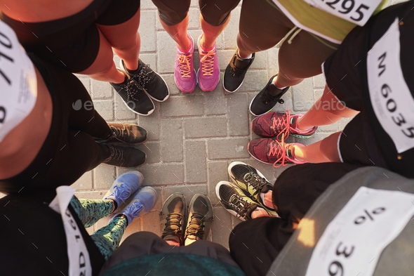 Feet of runners standing in a circle - Stock Photo - Images