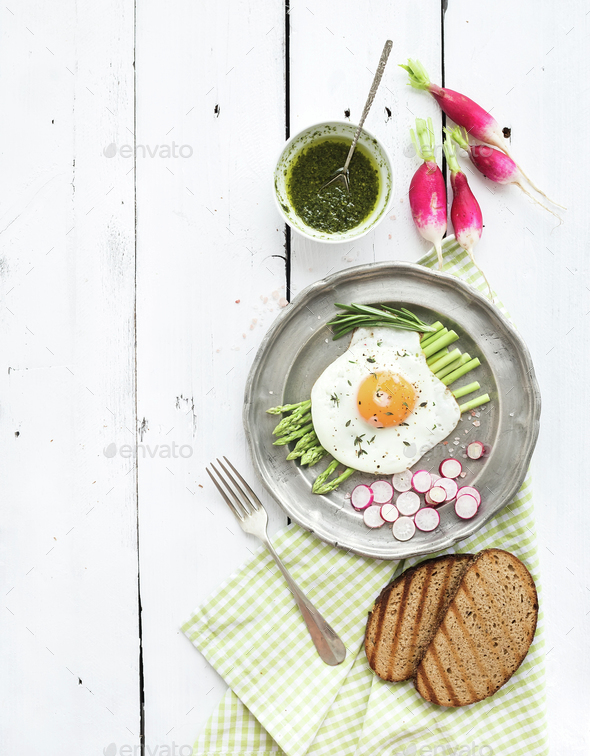 Healthy breakfast set. Fried egg with asparagus, radishes, green sauce and bread - Stock Photo - Images