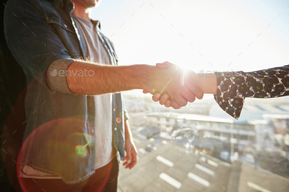 Shaking hands with lens flare - Stock Photo - Images