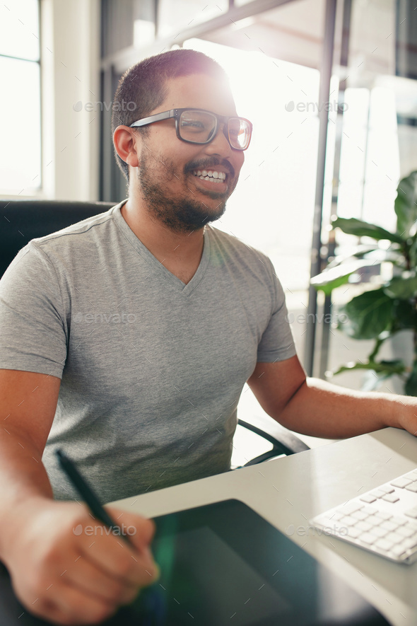 Happy graphic designer working in his office - Stock Photo - Images