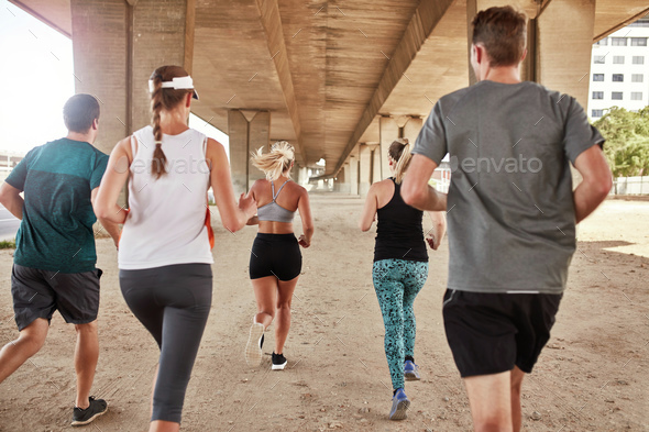Group of young men and women running together - Stock Photo - Images