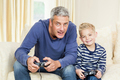 Father and son playing video games on the sofa - PhotoDune Item for Sale