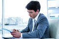 Concentrated asian businessman using his tablet in his office - PhotoDune Item for Sale