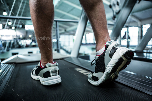 Cropped image of muscular man using treadmill at gym - Stock Photo - Images