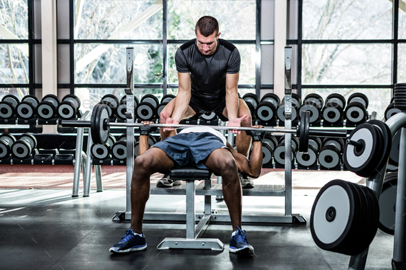 Trainer helping muscular man lifting barebell at gym - Stock Photo - Images